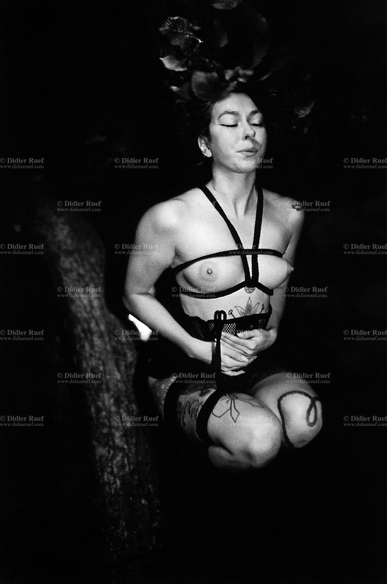 """Switzerland. Canton Valais. Vernayaz. Shibari at night in the forest. A nude woman with tattoos is tied with ropes on a tree's trunk. The contemporary meaning of Shibari describes an ancient Japanese artistic form of rope bondage. The art of erotic bondage, called Shibari, is an art of erotic spirituality. Shibari style rigging creates geometric patterns and shapes with rope that contrast beautifully with the human body's natural curves. The ropes and their texture provide contrast to smooth skin and curves. In Shibari, the model is the canvas, the rope is the paint and brush, and the rigger is the rope artist. Shibari experience results in an increased level of endorphins and other hormones, creating a trance-like experience for the model. When a Shibari scene is performed with appropriate ambience, these effects are actually visible in the face of the model. The term """"rope drunk"""" is sometimes affectionately used to describe the euphoric condition of the model after a Shibari experience. 23.07.2016 © 2016 Didier Ruef"""