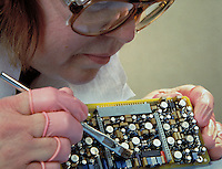Defense industry electronic component assembly. female worker. Lockheed, Martin.