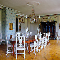 A blue and white tiled stove and dark armoire dominate this dining room