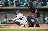 Birmingham Barons catcher Zack Collins (24) waits to receive a pitch in front of home plate umpire Jose Navas during a game against the Pensacola Blue Wahoos on May 8, 2018 at Regions FIeld in Birmingham, Alabama.  Birmingham defeated Pensacola 5-2.  (Mike Janes/Four Seam Images)