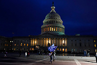 A supporter of President Donald Trump holds Trump flags stand outside the U.S. Capitol on Wednesday, Jan. 6, 2021, in Washington. (AP Photo/Jacquelyn Martin)