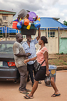 Nigeria. Enugu State. Enugu. Town center. A Igbo man working as street seller carries on his head a bucket with plastic household items. He is leaning against a Honda Accord car while talking to another Igbo man, a car mechanic, and smiling at a Igbo woman walking by. Flip-flops are a type of sandal, typically worn as a form of casual wear. They consist of a flat sole held loosely on the foot by a Y-shaped strap known as a toe thong that passes between the first and second toes and around both sides of the foot or can be a hard base with a strap across all the toes (these can also be called sliders). Enugu is the capital of Enugu State, located in southeastern Nigeria.  13.07.06.19 © 2019 Didier Ruef