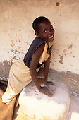 Kapatu, Zambia. Smiling girl pounding millet using a stone grindstone outside her house.