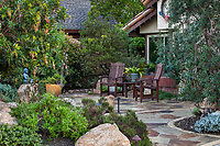 Chairs on front yard stone patio in California native plant garden; Vincent Garden