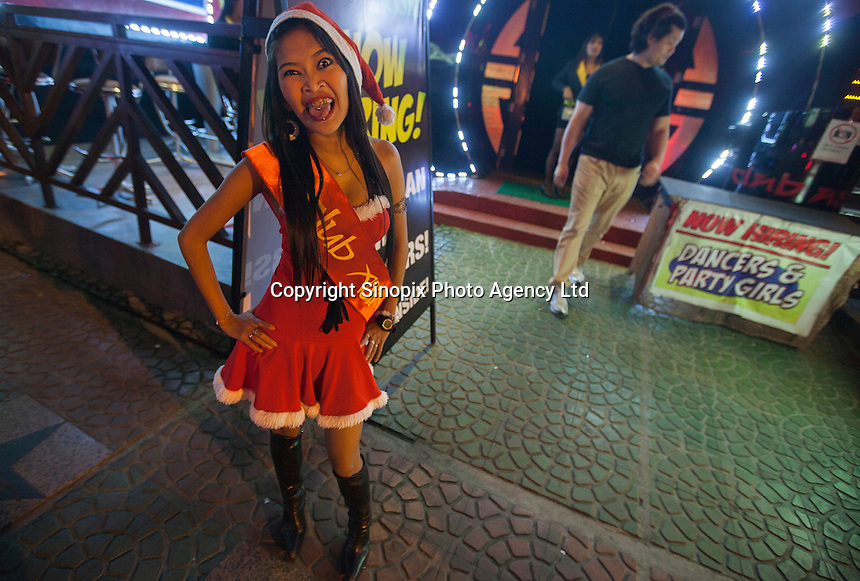 A prostitute wears a Christmas-themed santa outfit on Fields Avenue, the main strip of bars offering cheap prostitutes that runs through Angeles City, Republic of the Philippines, 08 November 2014. The 'sin city', which sprung up on the fringes of a US Air Force base during the Vietnam war, has a reputation for cheap sex, and was a favourite destination for alleged murderer Rurik Jutting, who used to fly to Angeles City from Hong Kong for debauched weekends. The British banker is currently on remand at a secure facility in Hong Kong for allegedly murdering two Indonesian prostitutes in his flat whilst high on alcohol and cocaine.