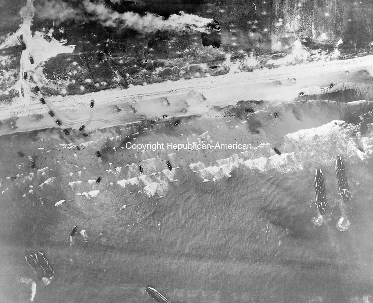 Men and assault vehicles storm the Normandy Beach of France, as allied landing craft arrive at their destination on D-Day, June 6, 1944. Note men coming ashore in surf and vehicles starting inland. (AP Photo)