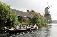 Schiedam- Noordvest met molens. Op de voorgrond de museummolen De Nieuwe Palmboom. Toeristen in een rondvaartboot
