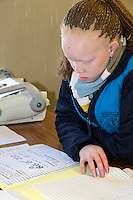 South Africa, Cape Town.  Visually-impaired African Albino Student Reading Student Workbook in English.  Athlone School for the Blind.