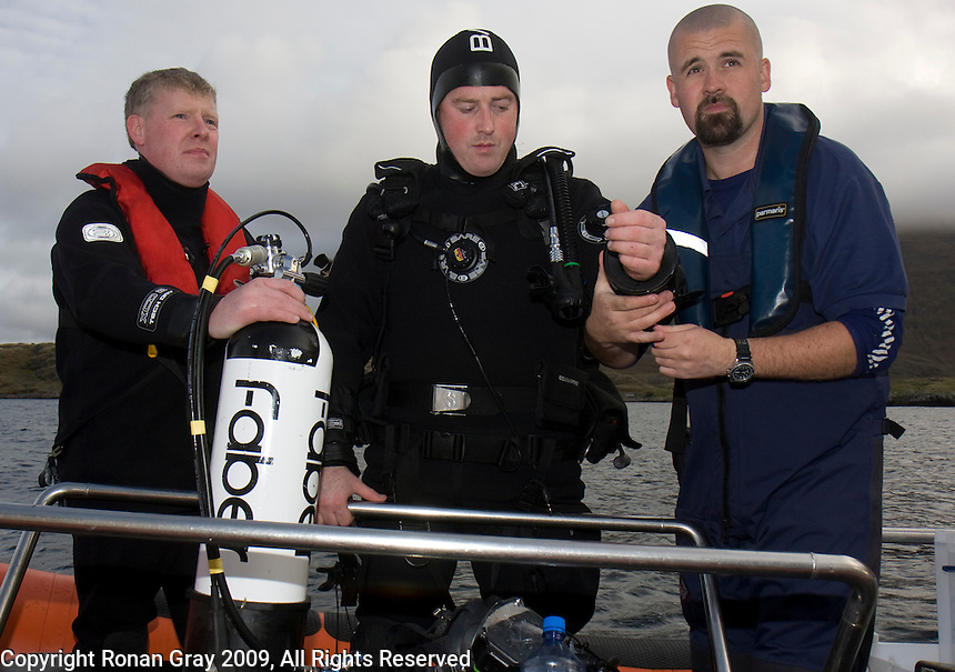 """Saturday Oct 10 2009.  SCUBADIVE WEST, GALWAY, IRELAND:  Dive supervisor Gary Jennings (L) and Commercial Diver Tiernan Gray (R) """"dress-in"""" Paul Devane before his world record attempt diver.  Brothers Declan and  Paul Devane began their world record attempt to be the first divers to stay underwater on SCUBA for a period of 24-hours at 10am this morning."""