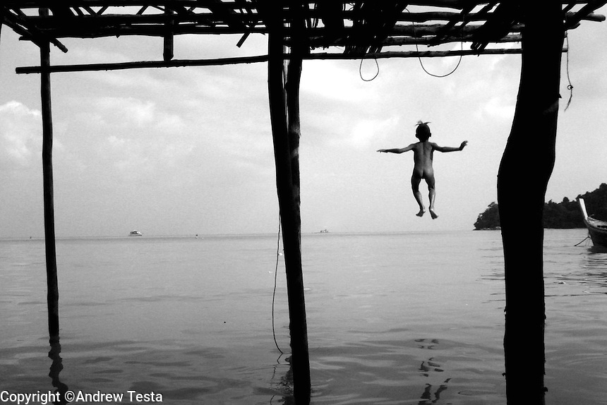 """THE MOKEN. 10.A boy jumps from his bamboo home, built on stilts above the water, into the sea.                               .The Moken are a nomadic tribe who live on the Surin Islands islands 60 km off the coast of Thailand. Recent scientific studies have shown that the underwater eyesight of Moken children is more than50% percent better than the underwater eyesight of other children. Scientists believe that the Moken train their eyes to see better out of necessity, they have to hunt for fish, and also make out things on the sea bed far below them. Experiments are now underway in Sweden to see if other children can train their eyes in a similar way. The Moken spend a large part of their time in the sea, and seem almost as at home in that environment as on land. At present they have no Family names or citizensip, but the Thai authorities have proposed that they all be given the same second name, roughly translated it means """"Hero of the Sea"""". The entire Moken population of the Surin Islands survived the recent Tsunami. News reports say that by the time the waves crashed ashore, the Moken were already on the higher ground and therefore safe. According to interviews they relied on the sayings of their ancestors which have been passed down through generations (they have no written language) which warn of the sea disappearing and then returning with a terrible force."""