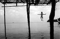 "THE MOKEN. 10.A boy jumps from his bamboo home, built on stilts above the water, into the sea.                               .The Moken are a nomadic tribe who live on the Surin Islands islands 60 km off the coast of Thailand. Recent scientific studies have shown that the underwater eyesight of Moken children is more than50% percent better than the underwater eyesight of other children. Scientists believe that the Moken train their eyes to see better out of necessity, they have to hunt for fish, and also make out things on the sea bed far below them. Experiments are now underway in Sweden to see if other children can train their eyes in a similar way. The Moken spend a large part of their time in the sea, and seem almost as at home in that environment as on land. At present they have no Family names or citizensip, but the Thai authorities have proposed that they all be given the same second name, roughly translated it means ""Hero of the Sea"". The entire Moken population of the Surin Islands survived the recent Tsunami. News reports say that by the time the waves crashed ashore, the Moken were already on the higher ground and therefore safe. According to interviews they relied on the sayings of their ancestors which have been passed down through generations (they have no written language) which warn of the sea disappearing and then returning with a terrible force."