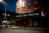 """Brooklyn, New York<br /> March 27, 2020<br /> <br /> Cobble Hill <br /> 7:52 PM - A theater normally crowded with movie goers on a Friday night.<br /> <br /> The coronavirus has transformed urban architectural spaces with proximity fear. Not entirely void of humanity, social distancing, within expansive city environments has created a landscape of aggrandizing physical structures and expanding spaces while diminishing the scale of humans. Face masks enhance the anonymity of """"the person"""", reducing them to a figure or an uninterrupted shadow falling on a surface."""