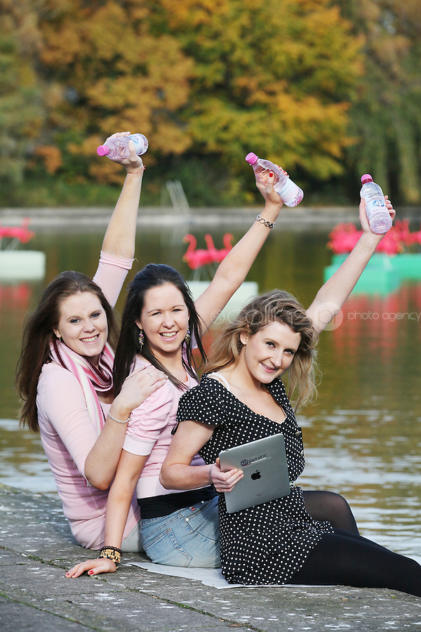 """NO Repro Fee.27/10/2010.  Ballygowan Pink's B Part Of It campaign in support of Breast Cancer Awareness Month. Hundreds of UCD students got behind Ballygowan Pink's B Part Of It campaign in support of Breast Cancer Awareness Month. Pictured are Sinead McAuliffe from Dublin, Regina Brady from Longford and Niamh Richardson from Dublin getting acquainted with some unusual pink guests on campus. As part of Ballgowan Pink's B Part Of It campaign, raising much need funded for the Marie Keating Foundation, over 100 """"pink flamingos"""" descended upon UCD lake this week to mark Breast Cancer Awareness Month. Picture James Horan/Collins Photos"""