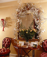A large gilded mirror in the hall is festooned with an organdie leaf garland with pearl branches and glittery white butterflies