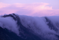 At dusk, as mountain air cools, low-level clouds form and silently  flow over ridges and into valleys below; complementary cloud shapes above suggest waveforms. Taken from Sunrise Point, Mount Rainier National Park, Washington State.....Photographed in 35mm format on Velvia 50 film.