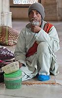 Fatehpur Sikri, Uttar Pradesh, India.  Man Offering Head-coverings to Men about to enter the Mausoleum of Sheikh Salim Chishti.
