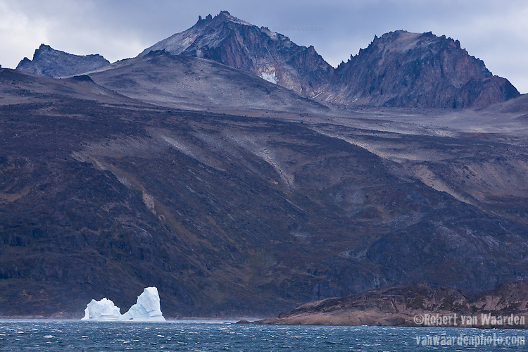 An iceberg with the naked mountains of Greenland in the background.