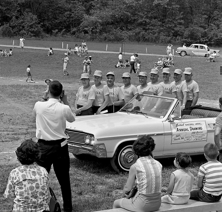 Bethel Park PA:  Members of the Bethel Park Athletic Association posing next to a car during the annual parade for the Bethel Baseball Association.  The BBA was very successful in teaching the young boys how to play baseball the right way.  The proof was that Bethel Park High School Baseball teams were some of the most successful in WPIAL history. Photo taken at the Bethel Park High School baseball field before the annual drawing of a new buick.
