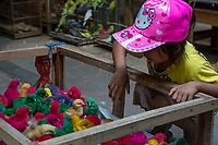 Yogyakarta, Java, Indonesia.  Young Girl Inspects Dyed Baby Chicks in the Bird Market.