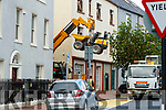 A digger being hoisted from a building in Ashe Street, Tralee