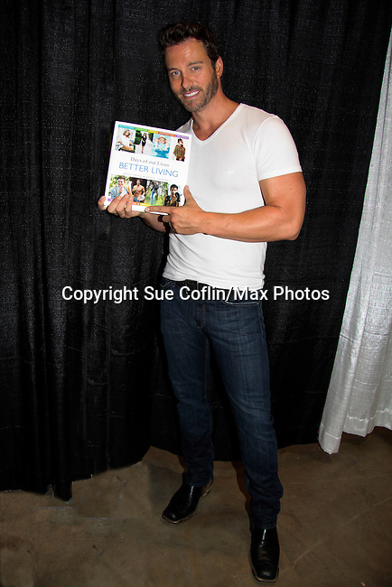 """Days of Our Lives Eric Martsolf """"Brady Black"""" holds the """"Days of Our Lives Better Living"""" as he appears at the 12th Annual Comcast Women's Expo on September 7 (also 6th), 2014 at the Connecticut Convention Center, Hartford, CT. He signed photos, posed with fans, walked the runway with models from Kathy Faber Designs Fashion Show, and broke some boards at Villari's Martial Arts Centers booth with Maggie and Ryan Farley.  (Photo by Sue Coflin/Max Photos)"""
