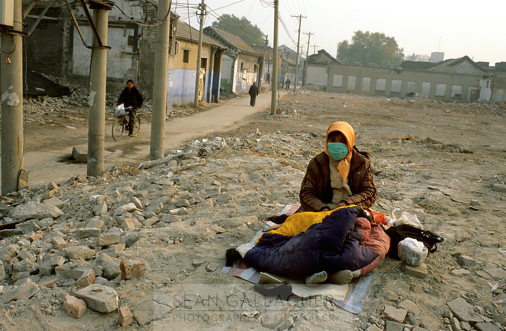 CHINA. Beijing. A homeless woman sits in the ruins of an old hutong (traditional home) in the central Qianmen district, destroyed to make may for new developments aimed at modernising the city for the 2008 Summer Olympics. 2005