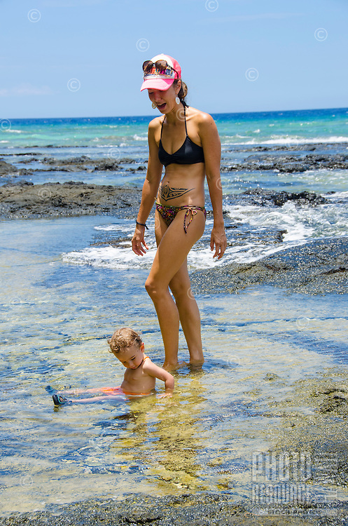 A local mother and son play in tide pools at a beach in Puako, South Kohala, Island of Hawai'i.