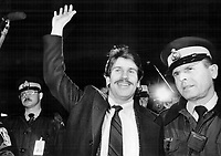 A jubilant Philip Engs waves at well-wishers as; escorted by a Mountie; he arrives in Toronto yesterday after being held more than two months in an Iranian prison as a suspected spy. The St. Catharines engineer insists that photos he took in Iran were personal; not espionage material.