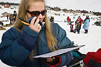 Volunteer checker Kaarin Andersson calls in dog traffic to the communications people at the White Mountain checkpoint during Iditarod 2008