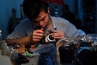 A man repairs a camera in Guangzhou, China.  ....