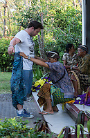 Bali, Indonesia.  Fitting a Visitor with a Sarong before Entering Uluwatu Temple Area to View Kecak dance.