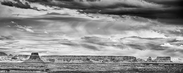 Monochrome infrared panoramic image of storm moving in over iconic desert landscape with sandstone buttes