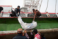Bangladeshi rescue workers carry the body of a victim of a ferry capsize during a rescue operation in the River Padma Sunday after being hit by a cargo vessel at Paturia , in Manikganj district, about 80 kilometers  northwest of Dhaka, Bangladesh. Feb. 23, 2015