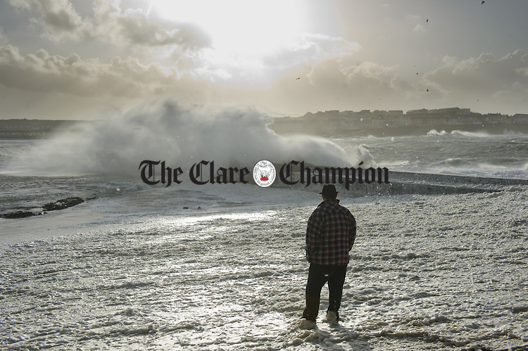 A loe man stands looking towards the pier in Kilkee as the waves pound and foam blows like snow during Storm Imogen. Photograph by John Kelly.