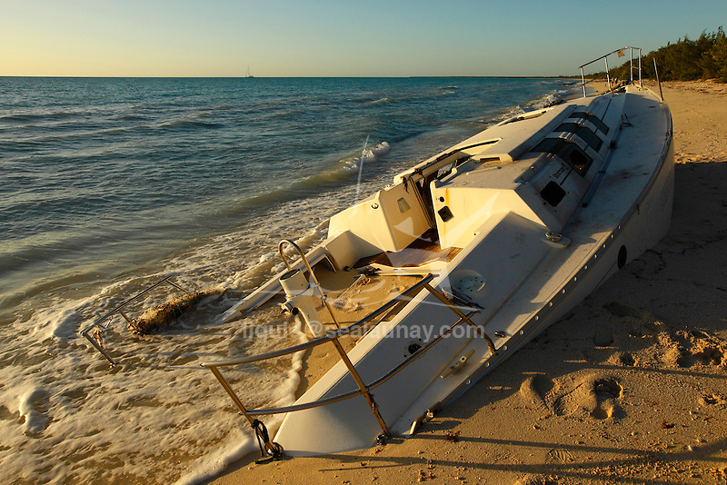 """The wreck of a Beneteau sailing yacht full of sand on the Fayaoue beach on the Ouvea island in the Loyalty islands..Ouvéa (local pronunciation: [u?ve.a]) is a commune in the Loyalty Islands Province of New Caledonia, an overseas territory of France in the Pacific Ocean. The settlement of Fayaoué [fa?jawe], on Ouvéa Island, is the administrative centre of the commune of Ouvéa..Ouvéa is made up of Ouvéa Island, the smaller Mouli Island and Faiava Island, and several islets around these three islands. All these lie among the Loyalty Islands, to the northeast of New Caledonia's mainland..Ouvéa Island is one of the Loyalty Islands, in the archipelago of New Caledonia, an overseas territory of France in the Pacific Ocean. The island is part of the commune (municipality) of Ouvéa, in the Islands Province of New Caledonia..The crescent-shaped island, which belongs to a larger atoll, is 50 km (30 miles) long and 7 km (4.5 miles) wide. It lies northeast of Grande Terre, New Caledonia's mainland..Ouvéa is home to around 3,000 people that are organized into tribes divided into Polenesian, Melanesian and Walisian by ethnic descend. The Iaai language is spoken on the island..The two native languages of Ouvéa are the Melanesian Iaai and the Polynesian Faga Uvea, which is the only Polynesian language that has taken root in New Caledonia. Speakers of Faga Uvea have fully integrated into the Kanak society, and consider themselves Kanak..Ouvéa has rich marine resources and is home to many sea turtles, species of fish, coral as well as a native parrot, the Uvea Parakeet, that can only be found on the island of Ouvéa..A large crustacaen called a """"coconut crab"""" or crabe de cocotier can also be found on the islands. The large crabs live in palm tree plantations and live solely on a diet of coconuts that they crack open with their powerful claws. They are blue in colour and can grow to several kilos in size. They are a land based species and do not venture into the ocean.."""