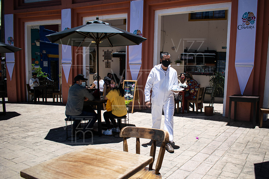 "BOGOTA - COLOMBIA, 05-09-2020: Un mesero atiende a los comensles durante el primer día del piloto de apertura de restaurantes y cafés al aire libre, denominado ""Bogotá a Cielo Abierto"", en el Chorro de Quevedo en el centro de Bogotá que ahora tiene sus calles pintadas con formas geométricas en pintura neón y cuenta con mesas, distribuidas estratégicamente para mantener el distanciamiento físico al finalizar la cuarentena total en el territorio colombiano causada por la pandemia  del Coronavirus, COVID-19. / A waiter serves the diners during the first day of the pilot for the opening of restaurants and outdoor cafes, called ""Bogotá a Cielo Abierto"", in Chorro de Quevedo in the center of Bogotá, which now has its streets painted with geometric shapes in neon paint and has tables, strategically distributed to maintain physical distancing at the end of the total quarantine in the Colombian territory caused by the Coronavirus pandemic, COVID-19. Photo: VizzorImage / Johan Rugeles / Cont"