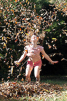 A girl plays in the leaves in Albemarle County, VA.