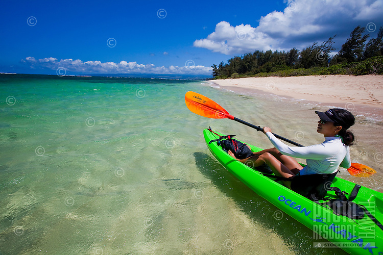 A young Asian woman paddling her kayak down the coast of Mokuleia