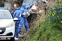 """Pictured: Forensics officers empty contents to a recycling skip at the house in Aberaeron, where the remains of a woman have been discovered in Ceredigion County, Wales, UK. Wednesday 21 March 2018<br /> Re: Human remains have been found in a house following a police investigation to find a missing woman.<br /> Police were called to the property in Aberaeron, west Wales after a woman in her 50s collapsed.<br /> Police also discovered the woman's mother, in her 80s, who had not been seen for some time.<br /> The women were named locally as Gaynor and Valerie Jones, with police currently treating the death as unexplained.<br /> The two women have ben described as """"reclusive"""" by neighbours and the home they shared as being """"heavily cluttered""""."""