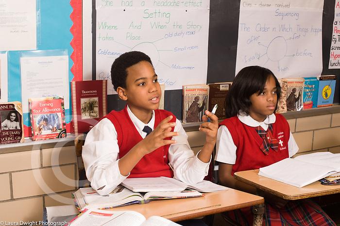 Parochial school 5th grade classroom male student talking in class, neighboring girl listening