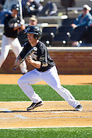 Andrew Williams (16) of the Wake Forest Demon Deacons lays down a bunt against the Youngstown State Penguins at Wake Forest Baseball Park on February 24, 2013 in Winston-Salem, North Carolina.  The Demon Deacons defeated the Penguins 6-5.  (Brian Westerholt/Four Seam Images)