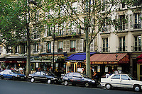 Eating places on tree-lined Boulevard St. Germaine; colorful awnings and glassed shelter for sidewalk tables. Apartments above have wrought iron balcony railings and grills on shuttered windows. Patrons and pedestrians. Paris, France.