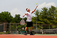 A young man tosses up a tennis ball prior to serving during a tennis match.