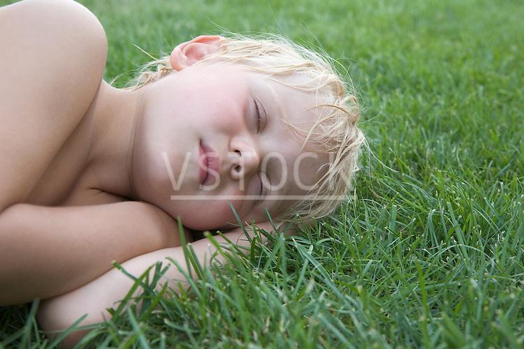 Boy (4-5) sleeping on grass