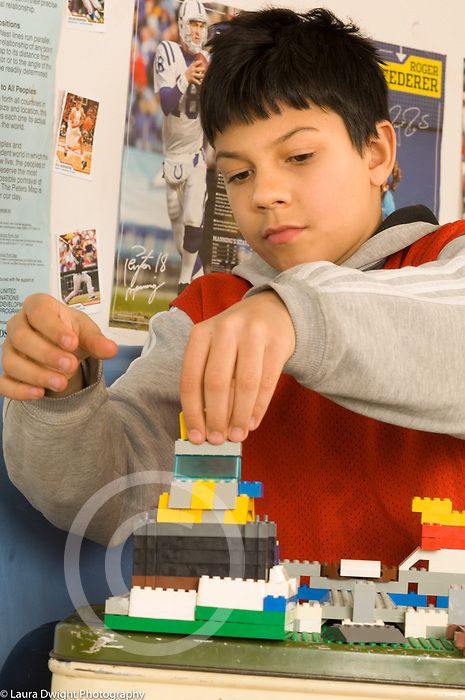 10 year old boy on bed in bedroom playing with construction Lego toys vertical
