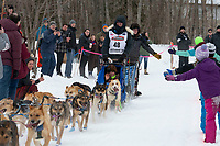 Riley Dyche and team run past spectators on the bike/ski trail near University Lake with an Iditarider in the basket and a handler during the Anchorage, Alaska ceremonial start on Saturday, March 7 during the 2020 Iditarod race. Photo © 2020 by Ed Bennett/Bennett Images LLC