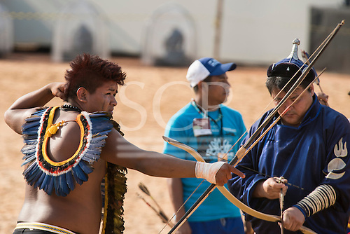 A Brazilian Bororo archer fires his arrow while a Mongolian contestant prepares during archery practice at the International Indigenous Games, in the city of Palmas, Tocantins State, Brazil. Photo © Sue Cunningham, pictures@scphotographic.com 28th October 2015