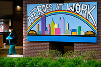 An employee of Children's Hospital walks out of the building past a sign that reads 'Heroes At Work' on Tuesday April 14, 2020 in Pittsburgh, Pennsylvania. (Photo by Jared Wickerham/Pittsburgh City Paper)