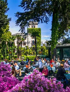 Schweiz, Tessin, Ascona am Lago Maggiore: Café Castello an der Promenade Piazza Giuseppe Motta mit Park und direkt am See gelegen | Switzerland, Ticino, Ascona at Lago Maggiore: cafe Castello at the seaside promenade Piazza Giuseppe Motta
