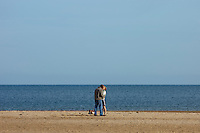 Holkham, Norfolk, England, 03/08/2009..Young couple kissing and dancing on Holkham beach.